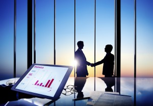 Silhouettes Of Two Businessmen Shaking Hands Together In A Board